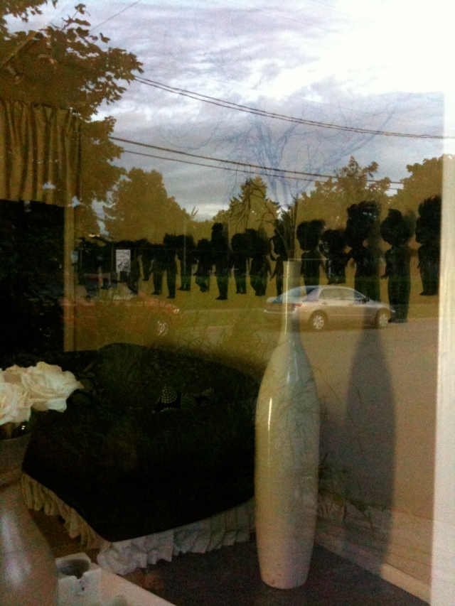 A photograph of a roomful of strangely assembled objects, seen through a window with reflections of the afternoon sky.